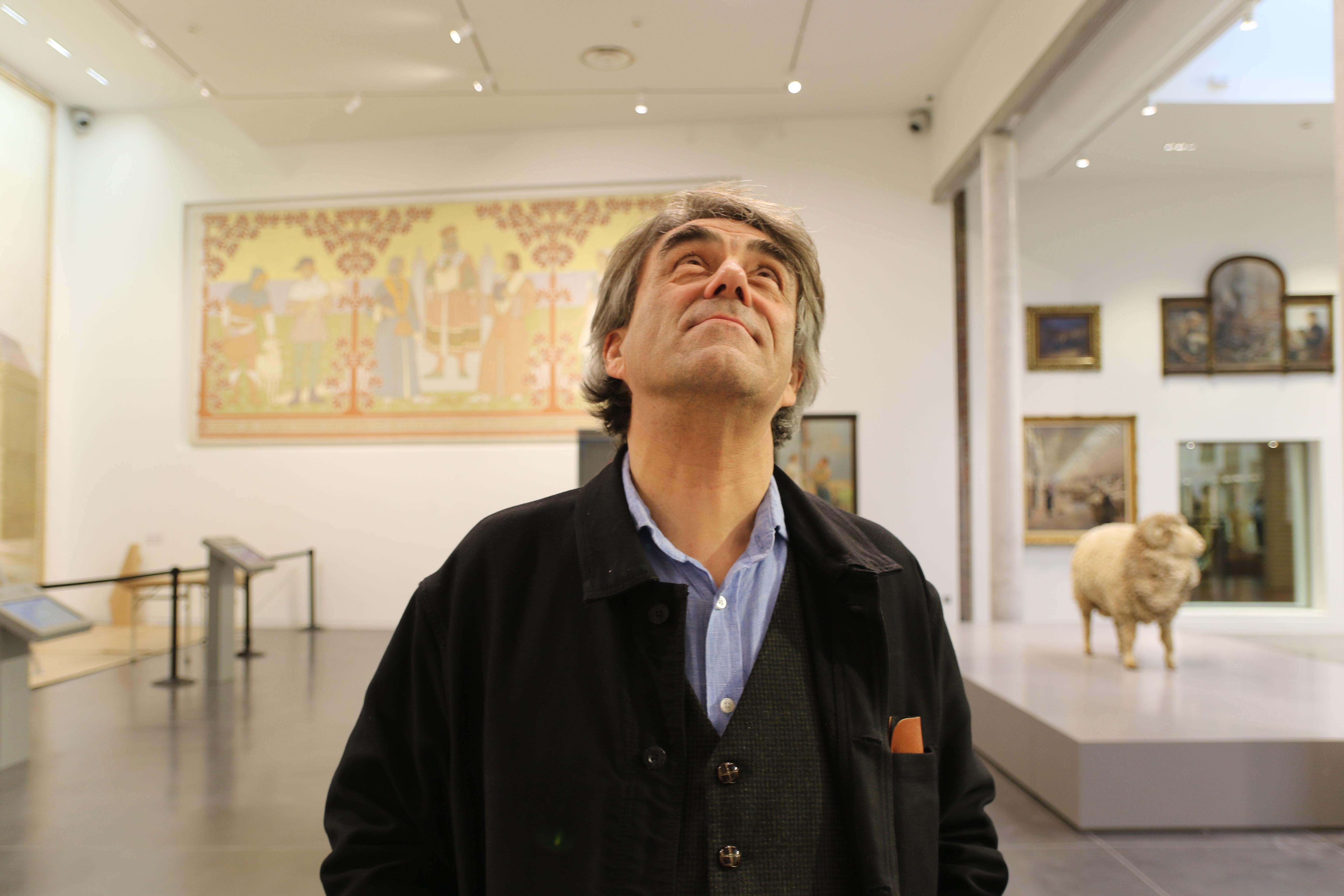 Bruno Gaudichon devant un tableau représentant la ville de Roubaix